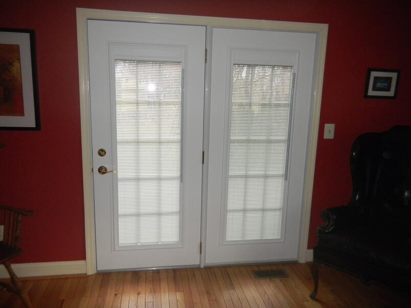 door with blinds between the glass