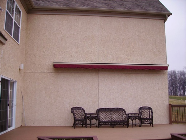 motorized retractable awning mounted on stucco wall
