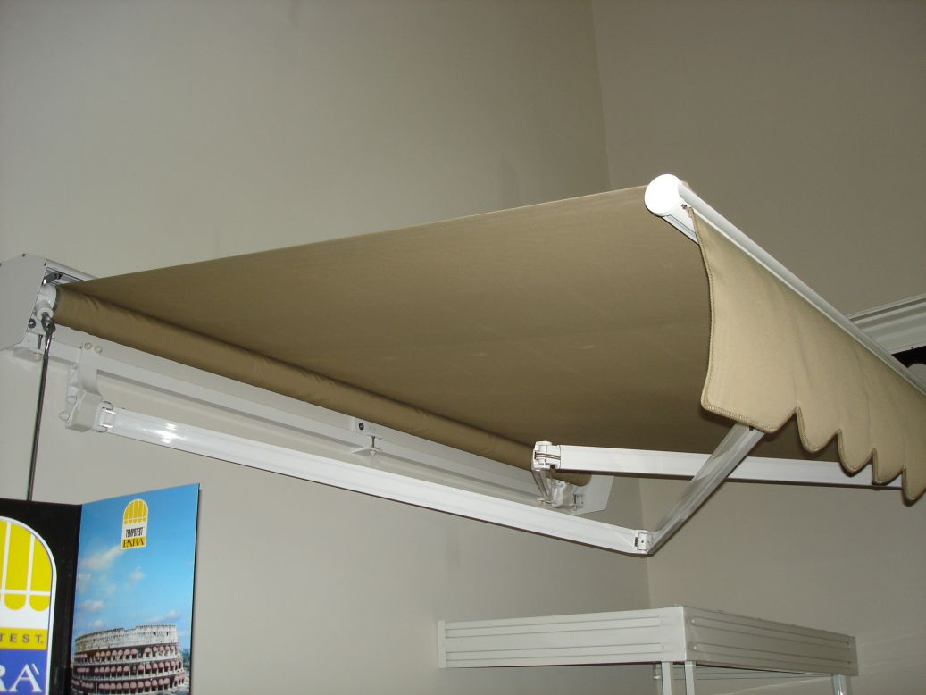 motorized retractable awning with crossover arms for extended length projection